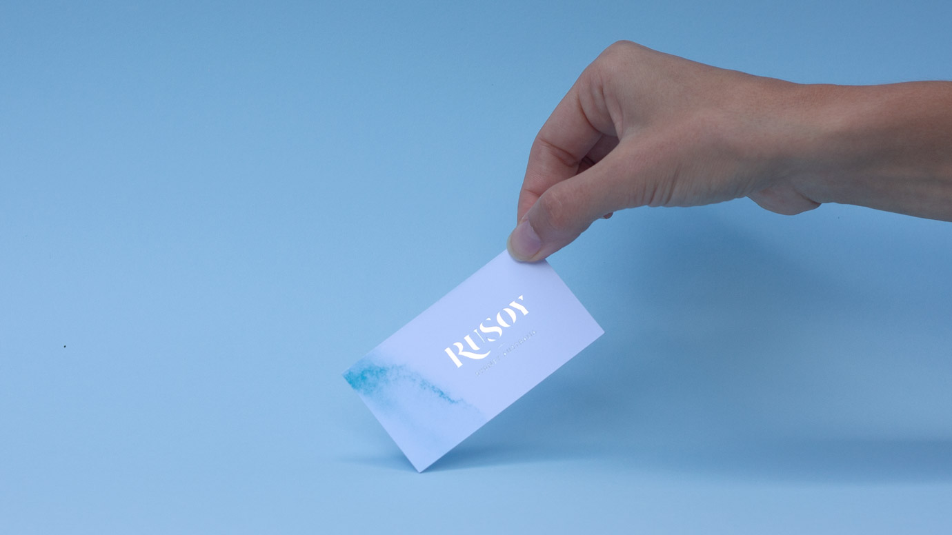 RuSoy Business Card held in a hand on a blue background